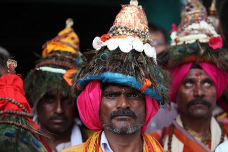 hombre viejo: Pune, India - 11 de julio 2015: Un grupo de peregrinos Vasudev que son devotos del Se�or Vishnu y llevan un sombrero c�nico con plumas de pavo real. Vasudev ha sido tradicional desde hace muchos a�os en Maharashtra. Estos peregrinos andan cantando alabanzas del Se�or Vishnu.