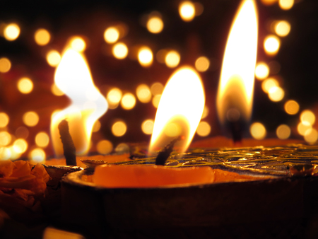 indian culture: Traditional Lamps lit on the occassion of Diwali festival on the backdrop of blur lights Stock Photo