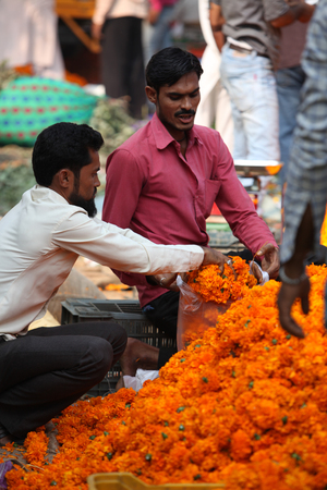 flower seller: Pune, India - October 21, 2015: A streetside flower seller packing Marigold flowers for a customer on the eve of Dassera festival in India in which these flowers are traditionally used. Editorial