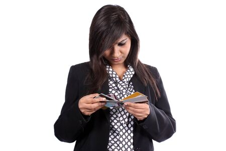 metaphorical: A metaphorical image of an Indian businesswoman confused in choosing from multiple credit cards she has.