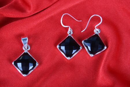 black onyx: A set of black onyx jewelery made in silver consisting of a pendant and a pair of earrings, on red fabric. Stock Photo