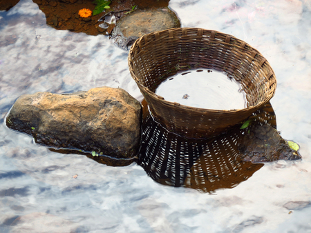lost lake: An empty cane basket abandoned on the rocks near a river stream Stock Photo