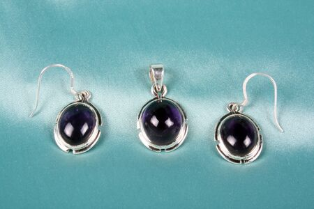 ear ring: A jewelery set of semi precious purple gemstones in silver pendant and earrings.