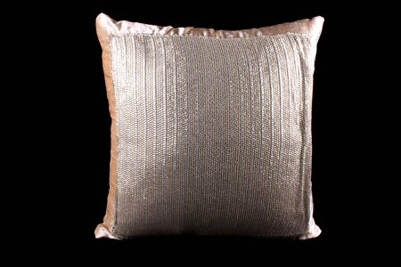 sequined: A golden and silver colored shiny pillow with sequins on black studio background.