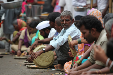 pune: Pune, India - July 11, 2015: Hungry pilgrims called warkaris wait to be served on the streets during the famous wari pilgrimmage in India.