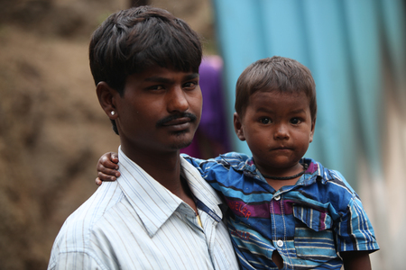 pune: Pune, India - July 16, 2015: A little boy with his poor father who is a construction worker, in India Editorial