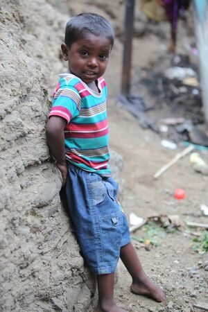 homeless children: Pune, India - July 16, 2015: A poor Indian boy standing at a construction site where his parents work in India