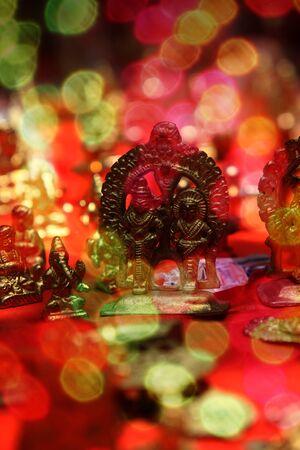 goddesses: Brass idols of hindu gods during festival, behind blur colorful lights. Stock Photo