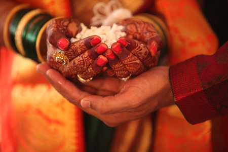 religion ritual: The hand of the bride held by a groom during a traditional ritual in an Indian Hindu Wedding Stock Photo