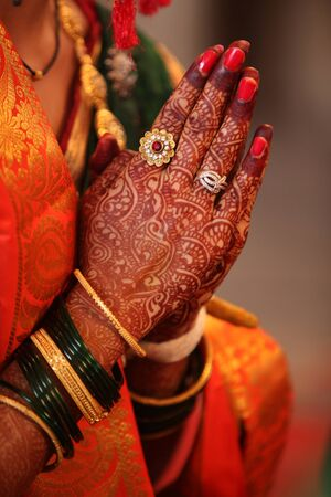 religion ritual: Folded henna decorated hands of an Indian bride during a prayer in a traditional Indian wedding