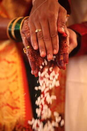 religion ritual: The hands of an Indian groom and bride performing a traditional wedding ritual.