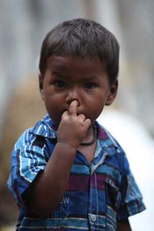 unhygienic: A poor little boy in blue shirt from India picking his nose.