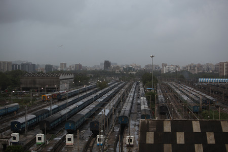 ariel: An ariel view of a train junction in India with many trains on the tracks.