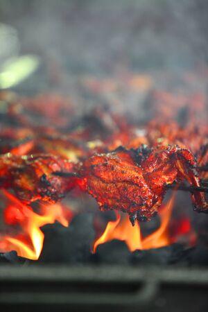 tandoori chicken: Delicious tandoori chicken being prepared on a grill in an Indian hotel.