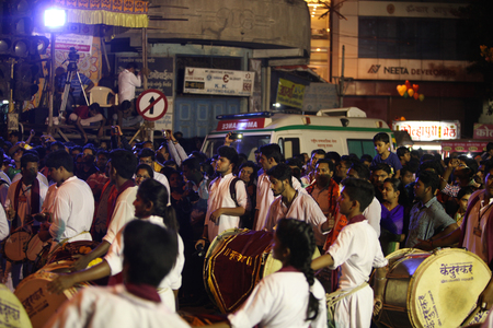 pune: Pune, India - September 27, 2015: People in India dancing on the streets on the beats of traditional percussion instrument dhol, during a huge procession in the Ganesh festival Editorial