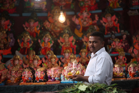 involves: Pune, India - September 16, 2015: A man selling Lord Ganesh idols on the eve of Ganesh festival in India. The festival involves thousands of visitors from all over the world every year, in the main celebration city - Pune. Editorial