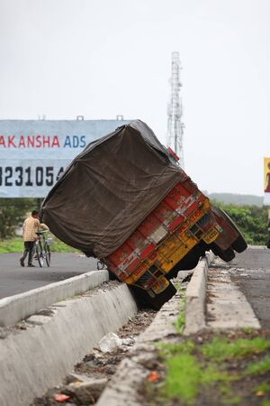 toppled: A truck toppled over into a drainage line during a freak accident in India.