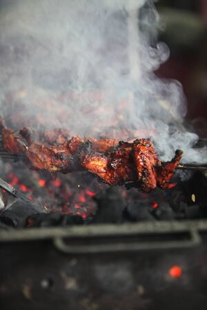 tandoori chicken: Delicious smoked tandoori chicken being prepared on a grill in an Indian hotel. Stock Photo