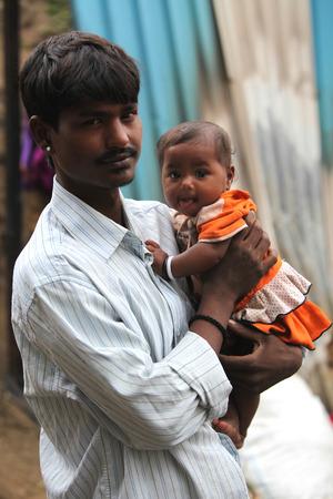 乳幼児: 愛情を込めて彼を見て、彼の幼い息子を持つ貧しいインド父親の肖像画。