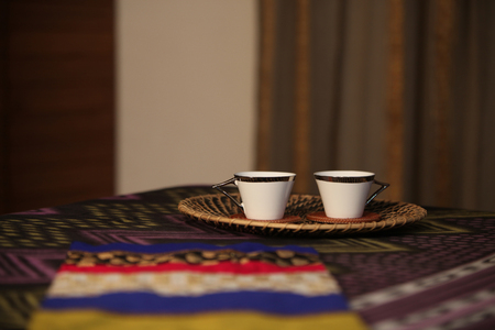 bedside: Bedside tea served in two cups in a tray, on a bed in a bedroom.