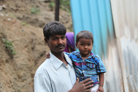 poor: A little boy with his poor father who is a construction worker, in India