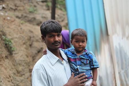 pobre: Un niño pequeño con su pobre padre, que es un trabajador de la construcción, en la India
