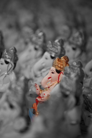 metaphorical: A metaphorical image showing a selected colorful lord Ganesha idol amongst many. Stock Photo