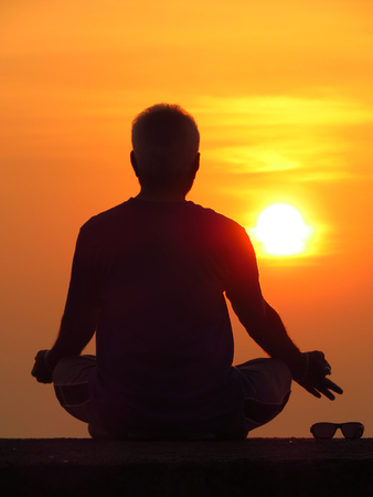 spiritualism: A man meditating against the setting sun a spiritual retreat during the summer holidays