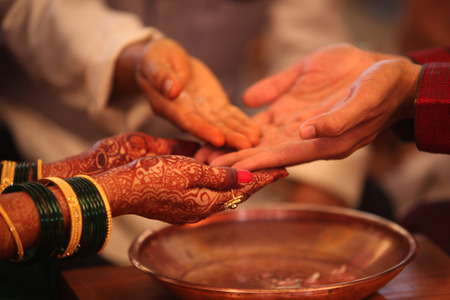 cérémonie de mariage: The hands of the bride and groom in a traditional Hindu wedding ritual