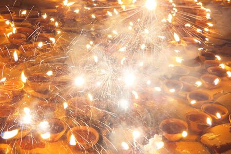 An abstract Diwali background of fireworks and sparklers on traditional lamps. Stock Photo