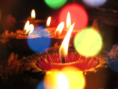 A view of traditional lit Diwali lamps for a ritual, through blur colorful lights.