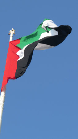 A huge flag of United Arab Emirates - UAE  fluttering in the wind, against clear blue skies.