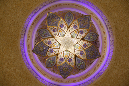 An beautiful chandelier with arabic design on the ceiling of the Grand Mosque in Abu Dhabi.