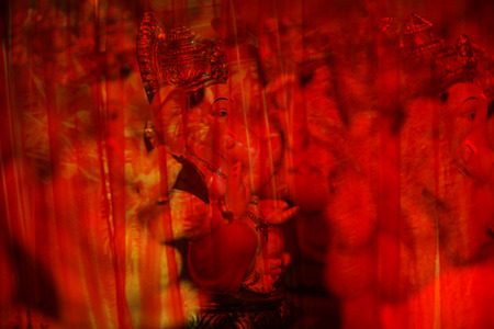 An abstract view of hindu elephant God Ganesha behind red transparent curtain Stock Photo