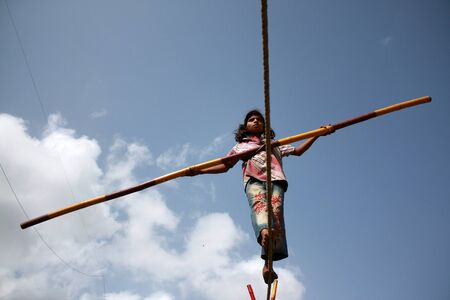 A street trapeze artist performs the balancing act on a tight rope in India. Editorial