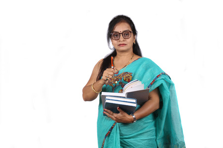 An Indian teacher with a book and pen giving explanation, on white studio background. Imagens