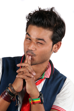 A young stylish Indian guy winking, on a white studio background