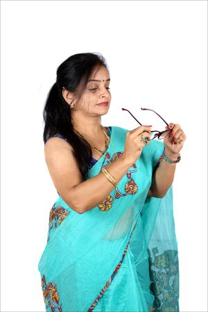 A beautiful Indian middleaged woman wearing her glasses, on white studio background.