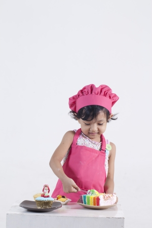 asian cook: little girl eating a cake