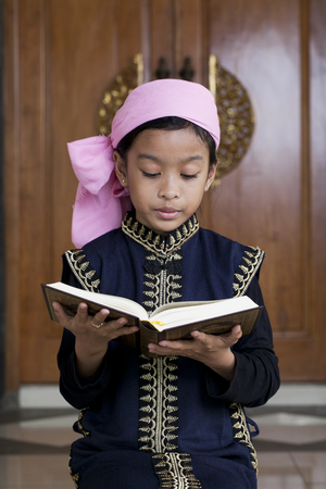 girl reading book of Quran