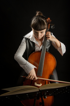 Girl Playing Cello Against Black Background photo
