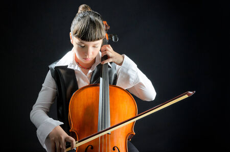 Girl playing the cello against a black background