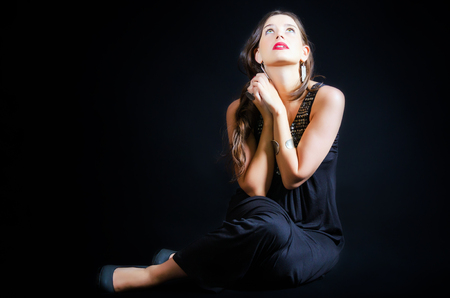 Sitting girl with hands in praying position against a black background Stock Photo