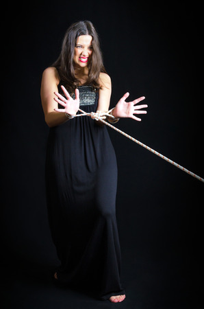 submissive: Girl posing with hands bound with rope against a black background Stock Photo
