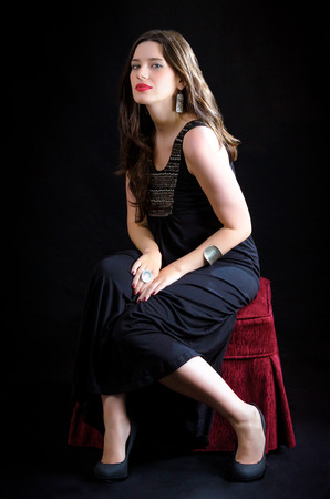 Attractive girl posing on a red chair against a black background