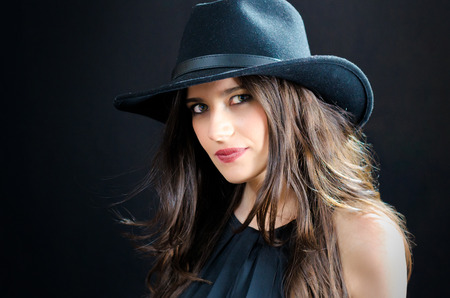 Portrait of an attractive young girl wearing a hat against a black background Stock Photo