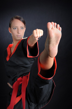 martial arts woman: Karate girl posing in kimono against a black background
