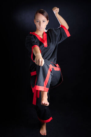 Karate girl posing in kimono against a black background