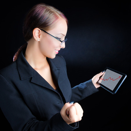 Attractive, young business woman looking at an ascending graph on a tablet computer against a black background