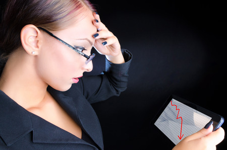Attractive, young business woman looking at a descending graph on a tablet computer against a black background